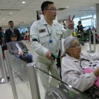 Lida Del Rosario, a Filipino living in California, passes through Taoyuan International Airport in Taiwan on Wednesday on her way to the Philippines to attend events during the visit of Pope Francis. | AP