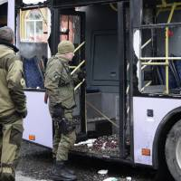 Pro-Russian rebels inspect a trolleybus that was shelled in Donetsk, Ukraine, on Thursday. The rebels said at least 13 people were killed. | AFP-JIJI