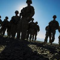 U.S. soldiers are silhouetted as they stand outside their vehicles during a mortar exercise near Forward Operating Base Gamberi in Afghanistan's Laghman province on Dec. 26. | REUTERS