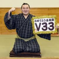 Mongolian yokozuna Hakuho poses with a placard celebrating his 33rd career championship on Friday.  | KYODO