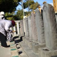 People offer joss ticks to the graves of the '47 ronin' samurai at Sengakuji temple in Tokyo on Jan. 8. The 47 ronin, who inspired the long-loved saga of loyalty and honor eulogized in films, books and plays, are fighting a new kind of battle in urban Japan. An apartment complex is going up next to the curved tile-roofed Sengakuji temple where the three-century-old graves of the ronin, or masterless samurai, lie. | AP