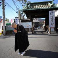 Monk Kenmyo Muta bows at the condominium construction site and the gate of Sengakuji temple in Tokyo on Jan. 8. The '47 ronin' samurai, who inspired the long-loved saga of loyalty and honor eulogized in films, books and plays, are fighting a new kind of battle in urban Japan. An apartment complex is going up next to the curved tile-roofed Sengakuji temple where the three-century-old graves of the ronin, or masterless samurai, lie. The banners at the temple gate reads: 'Against the construction.' | AP