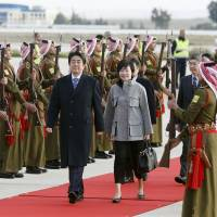 Prime Minister Shinzo Abe and his wife, Akie, are greeted by an honor guard at Queen Alia International Airport in the Jordanian capital of Amman on Saturday after flying from Cairo. Abe is on a six-day Middle East trip. | KYODO