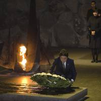 Prime Minister Shinzo Abe lays a wreath as his wife, Akie, stands behind him during a ceremony in the Hall of Remembrance at the Yad Vashem Holocaust memorial in Jerusalem on Monday. | REUTERS