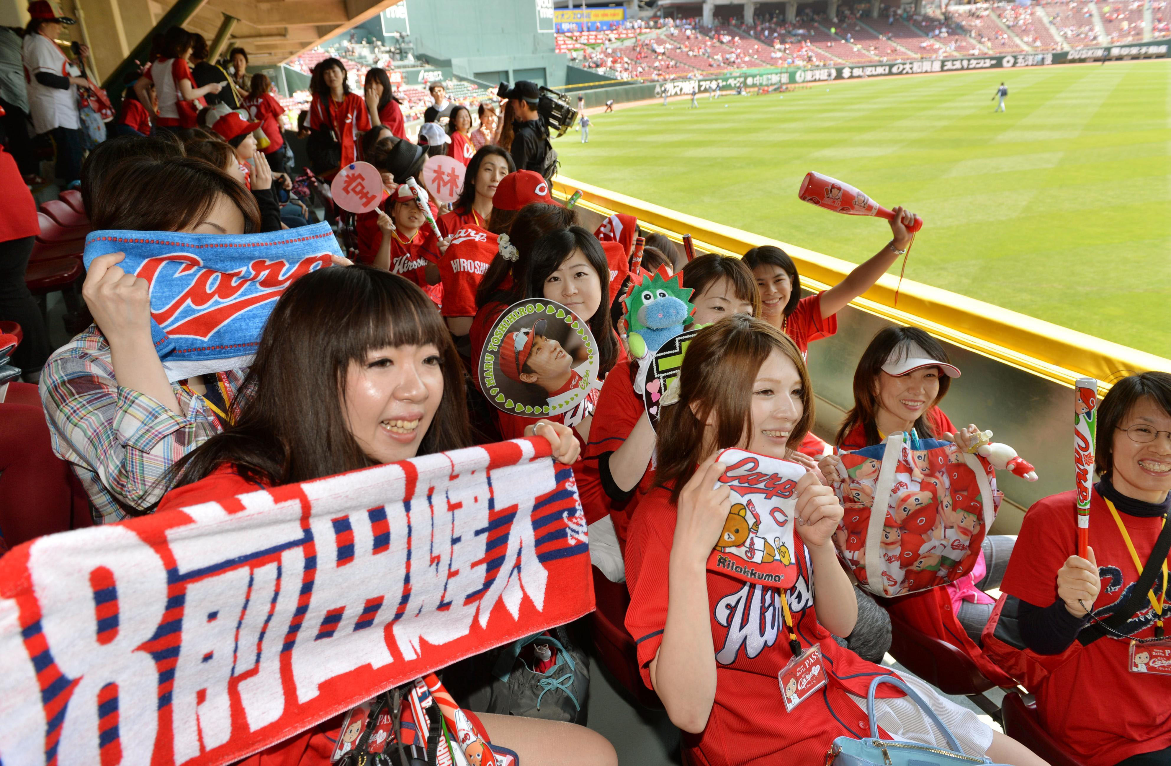 Female Hiroshima Carp fans from Kanto cheer their idols at Hiroshima's Mazda Stadium in May. They feel they have lifted the fortunes of the team and its handsome players.   KYODO