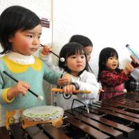 Children play with a xylophone in the music lobby of Kodomo-no-shiro in Tokyo's Shibuya Ward last Friday, ahead of the facility's closure. Below, young patrons and their parents listen to a music teacher inside the complex. | YOSHIAKI MIURA