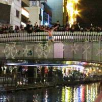 A man jumps from the Ebisubashi Bridge into the cold, polluted Dotonbori River in downtown Osaka early Thursday morning. Another man who had also apparently jumped in was later found unconscious. | KYODO