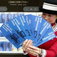 A staffer at the Toyota Automobile Museum shows off leaflets printed in 16 languages. | CHUNICHI SHIMBUN