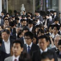 Morning commuters make their way to work in Tokyo in May 2010. Rush-hour crowds might turn into a thing of the past if crowdsourcing — the allocation of tasks to a remote group of workers online — becomes more common in Japan. | BLOOMBERG