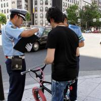 An officer issues a warning to a cyclist because his bicycle had brakes on only one wheel in Chuo Ward, Osaka, in August 2011. | KYODO