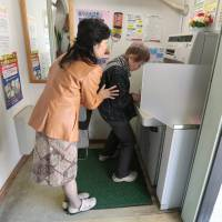 Yuriko Asahara, a retired manager of Japan Post Co.'s Nagabusa branch in Hachioji, Tokyo, helps a customer use an ATM last April. | BLOOMBERG
