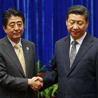 Prime Minister Shinzo Abe and Chinese President Xi Jinping share an awkward greeting Nov. 10 in Beijing. Experts say the wording of Abe's statement on the 70th anniversary of the end of World War II will have a major impact on Japan-China relations.   REUTERS