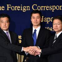 Candidates for the DPJ leadership (from left) Katsuya Okada, Goshi Hosono and Akira Nagatsuma join hands at the Foreign Correspondents' Club of Japan in Tokyo on Thursday. | AFP-JIJI