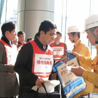 Mori Building Co. employees hand out bibs marked 'volunteer' to pretend evacuees during a disaster drill Friday. | KAZUAKI NAGATA