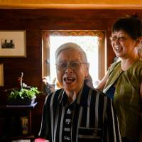 A woman diagnosed with Alzheimer's disease almost 10 years ago shares a laugh with her daughter in their apartment in Osaka on Aug. 6. The government estimates that about 7 million people aged 65 or older will be suffering from dementia in Japan by 2025.   BLOOMBERG