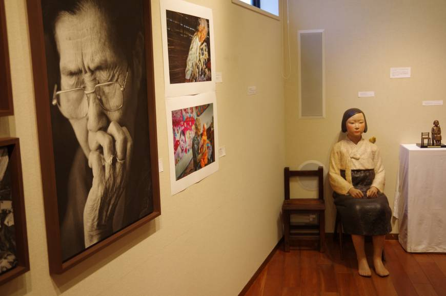 Photographs taken by Ahn Sehong of former 'comfort women' and a statue of a young girl who was forced to work in a wartime Japanese military brothel are displayed in Gallery Furuto in Nerima Ward, Tokyo, on Monday. | REIJI YOSHIDA