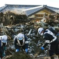 Workers shovel tsunami debris in Futaba on Dec. 17. The material was largely untouched since the town has been left uninhabitable due to elevated radiation levels. | KYODO