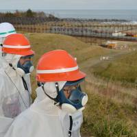 Shunichi Tanaka (right), head of the Nuclear Regulation Authority, visits a temporary radioactive dump that's being built within the Fukushima No. 1 plant. | POOL/KYODO