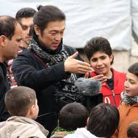 Freelance journalist Kenji Goto, believed to have been taken hostage by the Islamic State group, speaks with local children in Aleppo, northern Syria, in an undated file photo.   INDEPENDENT PRESS/KYODO