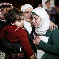 Anwar Tarawneh (right), the wife of Islamic State captive Jordanian pilot Lt. Muath al-Kasaesbeh, and his sister (center) weep after listening to a statement Wednesday released by Islamic State in front of the Royal Palace in Amman. Jordan is still holding Iraqi terrorist Sajida al-Rishawi, whose release has been demanded by Islamic State militants and her freedom depends on Kasaesbeh's fate. | REUTERS