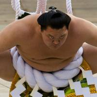 Mongolian-born grand sumo champion Hakuho performs the New Year's ring-entering rite at Meiji Shrine in Tokyo on Jan. 7. The yokozuna captured his 33rd Emperor's Cup last Friday, surpassing the legendary Taiho and becoming the sole leader on the career tournament victory list. | REUTERS