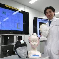 Ryohei Hasegawa, who leads a neurotechnology group at the National Institute of Advanced Industrial Science and Technology, poses with the Neurocommunicator on Dec. 4 in Ibaraki Prefecture. | KAZUAKI NAGATA