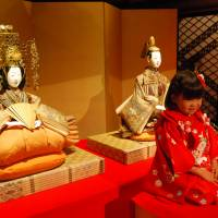 A pair of Hina dolls depicting the Imperial court are displayed behind a 4-year-old model as an annual exhibition kicked off Friday of some of the tiniest and biggest dolls in existence, at Meguro Gajoen's Hyakudan Kaidan in Tokyo. | JIJI