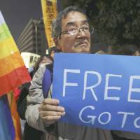 A man holds up a sign urging Prime Minister Shinzo Abe to try to save the life of Kenji Goto, a journalist being held hostage by the Islamic State group in Syria, during a rally outside Abe's office in Tokyo on Sunday. | AP