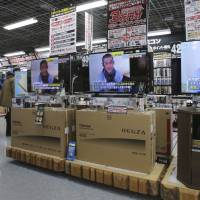 A sales clerk walks by TV sets broadcasting news about detained hostage Kenji Goto at an electronics store in Tokyo on Friday. The ransom deadline for two Japanese hostages held by the Islamic State group presumably passed on Friday. | AP