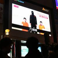 Pedestrians in Tokyo on Friday pass a monitor showing a news report on the two Japanese hostages held by the Islamic State group.   AP