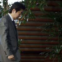 Prime Minister Shinzo Abe walks through his official residence in Tokyo on Friday, after a deadline for a prisoner swap purportedly set by the Islamic State group passed with no word on the hostages' fate. | AP