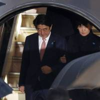 Prime Minister Shinzo Abe and his wife, Akie, disembark from a plane at Tokyo's Haneda airport on Wednesday. | REUTERS