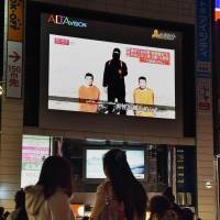 People watch a large TV screen in Tokyo on Tuesday showing news reports about the two Japanese men (kneeling) being held by the Islamic State group. | AFP-JIJI