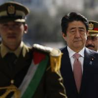 Prime Minister Shinzo Abe visits the tomb of the late Palestinian leader Yasser Arafat at the Palestinian Authority's headquarters in the West Bank city of Ramallah on Tuesday. | AFP-JIJI