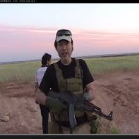 Haruna Yukawa, one of two Japanese hostages held by the Islamic State group, appears in a video on his YouTube channel handling an AK-47 last year in Aleppo, Syria. He has described himself as a security professional, but his motives for wanting to join militants there remain unclear. | YOUTUBE