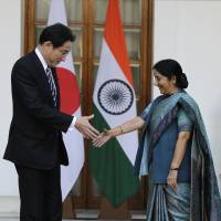 Foreign Minister Fumio Kishida and Indian Foreign Minister Sushma Swaraj greet each other before the start of a meeting n New Delhi on Saturday. | AP