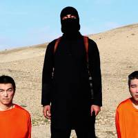 In this screen grab from an online video released by the Islamic State group's media arm on Tuesday, hostages Kenji Goto (left) and Haruna Yukawa are seen kneeling beside a knife-wielding militant. The group has threatened to kill the two Japanese unless a $200 million ransom is paid within 72 hours. | AP