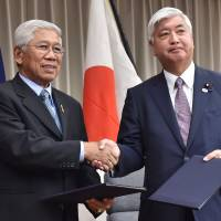 Defense Minister Gen Nakatani (right) and Philippine Defense Secretary Voltaire Gazmin exchange documents on their bilateral defense cooperation during a signing ceremony at the Defense Ministry in Tokyo on Thursday. Gazmin is on a three-day visit to Japan.   AFP-JIJI