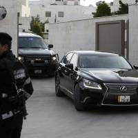 A Jordanian policeman stands guard as vehicles, part of a convoy carrying Japanese envoy Yasuhide Nakayama, leaves the Japanese Embassy in Amman on Saturday. | REUTERS