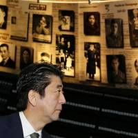 Prime Minister Shinzo Abe looks at pictures of Jewish Holocaust victims at the Hall of Names during a visit Monday to the Yad Vashem Holocaust History Museum in Jerusalem commemorating the 6 million Jews killed by the Nazis during World War II. | POOL/AFP-JIJI