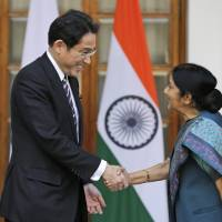 Foreign Minister Fumio Kishida shakes hands with Indian Foreign Minister Sushma Swaraj ahead of their meeting in New Delhi on Saturday. | AP