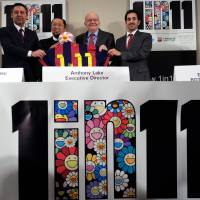 FC Barcelona President Josep Maria Bartomeu, artist Takashi Murakami, UNICEF Executive Director Anthony Lake and Reach Out To Asia Director Essa al-Mannai (left to right) pose with a jersey reading '1 in 11' during the launch of the eponymous campaign in New York on Friday. The initiative aims to get marginalized children in Bangladesh, Indonesia and Nepal into education. | AFP-JIJI
