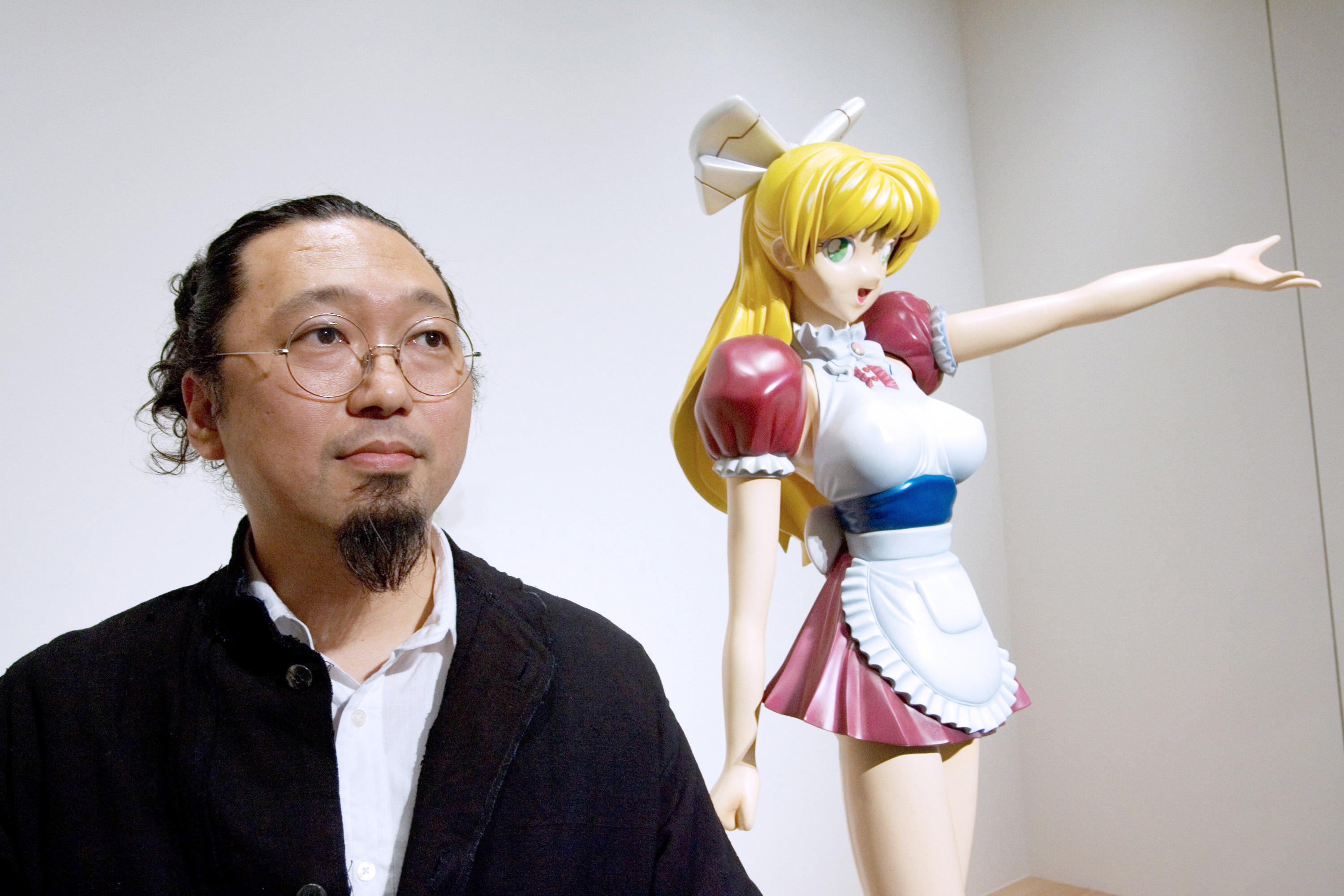 Contemporary artist Takashi Murakami poses with his 'Miss ko2' sculpture at a gallery in Tokyo in July 2007.   BLOOMBERG