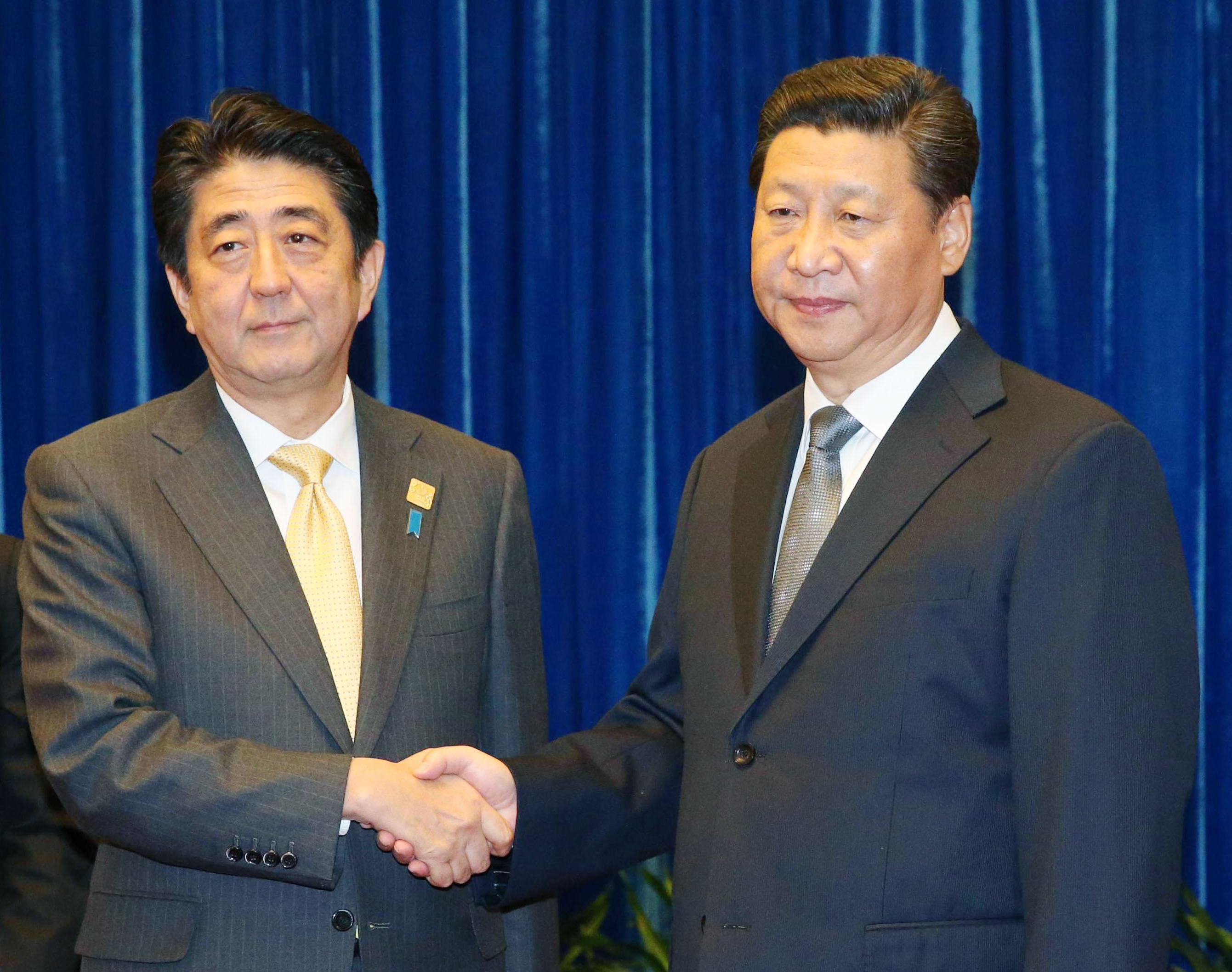 Prime Minister Shinzo Abe and Chinese President Xi Jinping shake hands in November before talks in Beijing. The long-delayed meeting marked a breakthrough in bilateral ties that froze after Japan effectively nationalized the Senkaku Islands. | KYODO