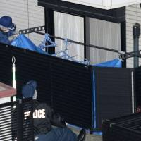 Police investigate the apartment of a 19-year-old female college student Tuesday in Showa Ward, Nagoya, after the body of an elderly woman was found there. | KYODO