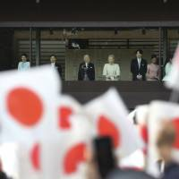 Emperor Akihito, Empress Michiko and other members of the Imperial family greet well-wishers from behind bulletproof glass on a balcony at the Imperial Palace during their traditional New Year's appearance Friday. | AP