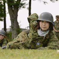Women crawl forward during the annual boot camp simulation held for curious civilians at the Ground Self-Defense Force's Northern Army headquarters in Eniwa, Hokkaido, in July 2012.   KYODO