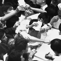 Traders at the Tokyo Stock Exchange celebrate after the Nikkei stock average closed at a record high of ¥38,915 on Dec. 29, 1989. | KYODO