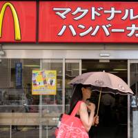 A woman passes a McDonald's outlet in Tokyo in July. Diners in the capital and in Misawa, Aomori Prefecture, have reported finding pieces of vinyl in Chicken McNuggets. | BLOOMBERG