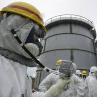 A Tokyo Electric Power Co. worker measures radiation levels in the H4 tank area at the Fukushima No. 1 nuclear power plant in Okuma, Fukushima Prefecture, in November 2013. Radioactive water leaked from one of the storage tanks there last August. | AP